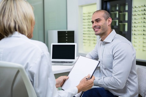 Middle-Aged Man Discussing Details of Cataract Surgery with Doctor